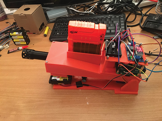 ... The 3D-printed lid has a slot to load the upside-down Nerf gun  magazine. A roller underneath moves along to tilt the whole mechanism up  and down to aim.